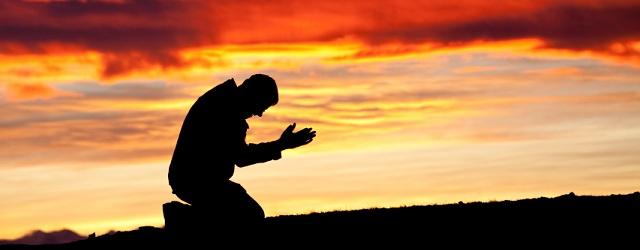 homem orando de joelhos